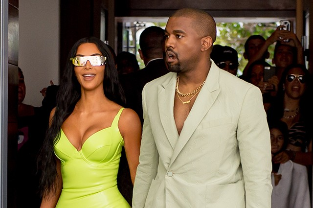 Kim Kardashian shined extra bright in neon and she and Kanye West arrive at Miamis Versace Mansion for rapper 2Chainz Wedding on Saturday